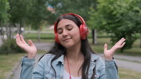 Beautiful cheerful girl dancing in the park listening to music on headphones. Fun mood. Beautiful cheerful happy girl in denim clothes dancing in the park during stock video footage