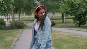 Beautiful cheerful girl dancing in the park listening to music on headphones. Beautiful cheerful happy girl in jeans clothes dancing in the park listening to stock video