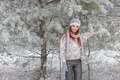 Beautiful cheerful happy girl with red hair in a warm hat and scarf playing and fooling around in the snow in the winter forest Stock Images