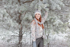 Beautiful cheerful happy girl with red hair in a warm hat and scarf playing and fooling around in the snow in the winter forest Royalty Free Stock Images