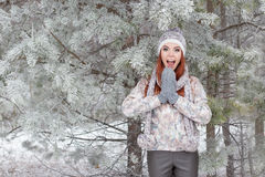 Beautiful cheerful happy girl with red hair in a warm hat and scarf playing and fooling around in the snow in the winter forest Royalty Free Stock Image