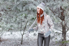 Beautiful cheerful happy girl with red hair in a warm hat and scarf playing and fooling around in the snow in the winter forest Royalty Free Stock Photography