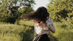 Beautiful cheerful happy young girl wearing black skirt with wavy hair walks in the path in forest scatters hair and stock video