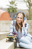 Beautiful cheerful hipster girl listening music in the street. Royalty Free Stock Images