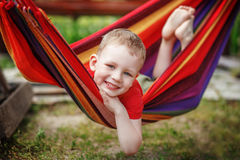 Beautiful cheerful little boy resting in a hammock Royalty Free Stock Images