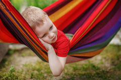 Beautiful cheerful little boy resting in a hammock Royalty Free Stock Image