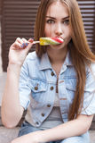 Beautiful cheerful sexy cute red-haired girl eating colored ice cream on city streets Royalty Free Stock Images