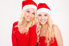 Beautiful cheerful sisters twins in santa claus clothes and hats Stock Image