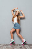 Beautiful cheerful smiling girl in hat and roller skates posing Stock Photos