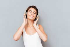 Beautiful cheerful smiling woman listening to music with headphones Stock Photos