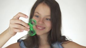Beautiful cheerful teen girl playing with green fidget spinner on white background Stock Photo