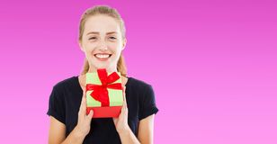 Beautiful cheerful woman in black t shirt giving you present box over purple background, holidays concept,copy space stock images