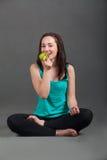 Beautiful cheerful woman eating an apple. Beautiful cheerful woman eating a green apple Stock Photos