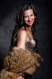 Beautiful cheerful woman in a fur coat. On a black background Stock Images