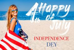 Beautiful cheerful woman holding an American flag on the beach royalty free stock photos