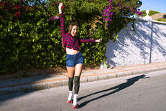 Beautiful cheerful woman on roller skates crying 'Hurrah'. Portrait of beautiful cheerful woman on roller skates crying 'Hurrah' while standing on the sunny Stock Photo