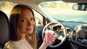 Beautiful cheerful girl sits in the car, drinks coffee and laughs. Beautiful cheerful woman sits in the car, drinks coffee and laughs stock video