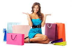 Beautiful cheerful woman sitting among shopping bags. Beautiful excited woman sitting among colorful shopping bags Royalty Free Stock Images