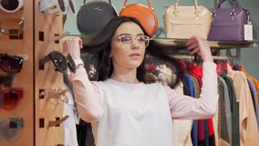 Beautiful cheerful woman smiling to the camera, trying on glasses while shopping. Attractive long haired woman enjoying shopping for eyewear. Retail, sale stock video