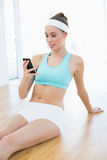 Beautiful cheerful woman in sportswear using her smartphone Royalty Free Stock Photography