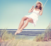 Beautiful Cheerful Woman Swinging by the Beach Royalty Free Stock Photo