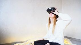 Beautiful and cheerful women immersed in virtual reality in spec. Modern girl visits different places and looks through streets of virtual reality with help of Stock Photo