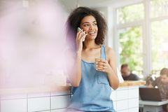 Beautiful cheerful young african girl student smiling talking on phone drinking coffee in cafe. Stock Photography