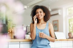 Beautiful cheerful young african girl student smiling talking on phone drinking coffee in cafe. Stock Images