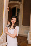 Beautiful and cheerful young bride posing in luxurious vintage interior near doorcase Stock Photography
