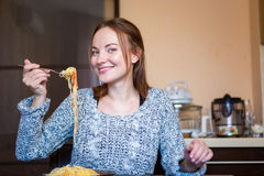 Beautiful cheerful young female eating pasta in kitchen Royalty Free Stock Images