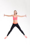 Beautiful cheerful young sportswoman jumping in the air Stock Photos