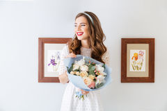Beautiful cheerful young woman with bouquet of flowers Stock Images