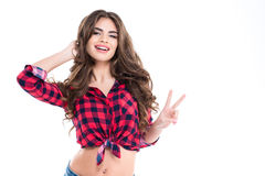Beautiful cheerful young woman in checkered shirt showing victory sign Stock Photography