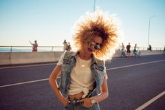 Beautiful and cheerful young woman with lush hair, outdoors Royalty Free Stock Image