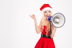 Beautiful cheerful young woman talking in speaker and pointing away Stock Photos