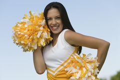 Beautiful Cheerleader Holding Pom-Poms Royalty Free Stock Images