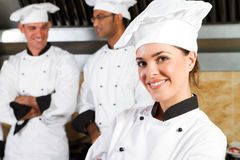 Beautiful chef. A beautiful young professional chef in kitchen with her colleagues in the background Stock Image