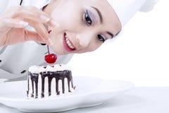 Beautiful chef decorating cake. Beautiful chef decorating chocolate cake on white background stock photos