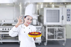 Chef holds delicious cake - horizontal. Beautiful chef is holding fruit cake at the kitchen , horizontal shot royalty free stock image