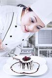 Chef preparing dessert. Beautiful chef is preparing a chocolate dessert in the kitchen royalty free stock photography
