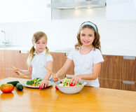 Beautiful chef sisters at kitchen preparing salad Stock Photography