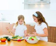 Beautiful chef sisters at kitchen preparing salad. Beautiful chef sisters at home kitchen preparing salad stock photos