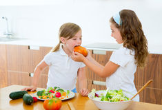Beautiful chef sisters at kitchen preparing salad Royalty Free Stock Photography