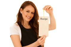 Beautiful chef woman holding a card with recipe isolated over wh. Ite background Royalty Free Stock Photography