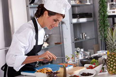 Beautiful chef working on her dishes. Beautiful chef preparing an amuse with pincers Stock Photography