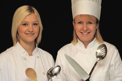 Beautiful Chefs. A portrait of two beautiful chefs holding kitchen tools, on a black background Stock Photography