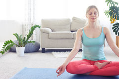 Beautiful chestnut practicing lotus pose on yoga mat indoor Royalty Free Stock Photography