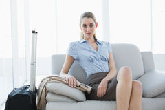 Beautiful chic businesswoman posing sitting on couch next to her suitcase Stock Image