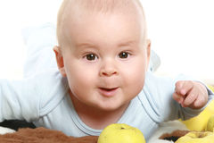 Beautiful child in apples. On a fluffy carpet royalty free stock photos