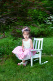 Beautiful Child on Beautiful Morning. Beautiful little girl poses on Easter Sunday morning. She is wearing a pink and white gingham dress with net slip. Her hair stock image